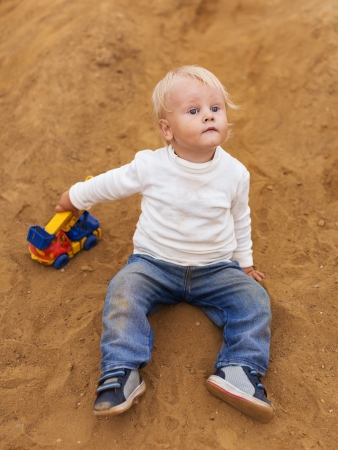 cute little baby boy playing in the sandbox on the playground  photo