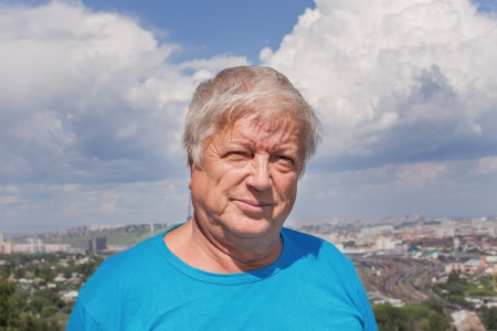 Portrait of the senior man against a city of Krasnoyarsk photo