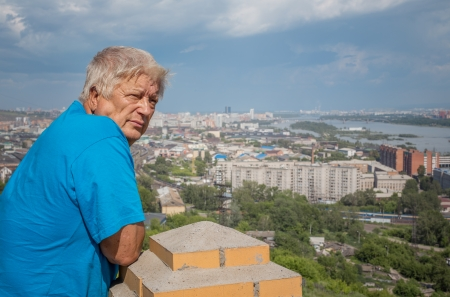 The elderly man looks at a city Krasnoyarsk and the river photo