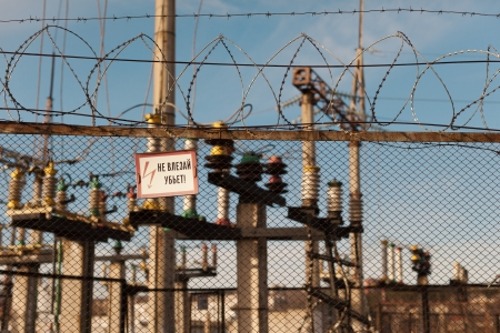 High-voltage transformer substation behind barbed-wire chain-link fence with Danger High Voltage sign.  photo