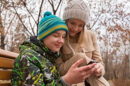 happy teenagers: Happy teenagers couple reading a mobile text message. Stock Photo