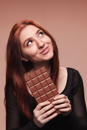Portrait of the young girl with  big chocolate Banco de Imagens