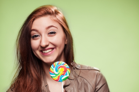 Portrait of the girl teenager with a sugar candy on a stick on a green background Stock Photo
