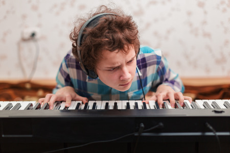 A shot of teenager boy playing piano  photo