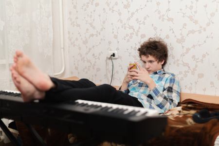 The boy plays phone, having put feet on the piano photo