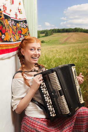 Russian girl in national dress playing the accordion photo