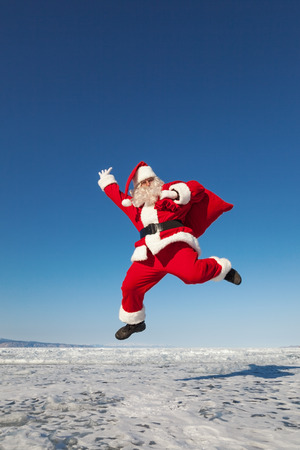 conducted: Santa Claus joyously jumping in the snow,  shooting was conducted in a sunny day on lake Baikal