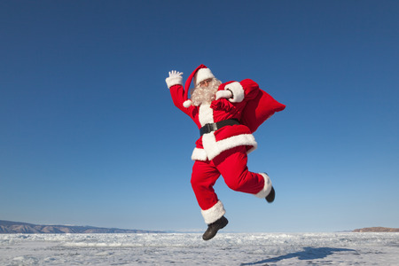 Santa Claus joyously jumping in the snow,  shooting was conducted in a sunny day on lake Baikal