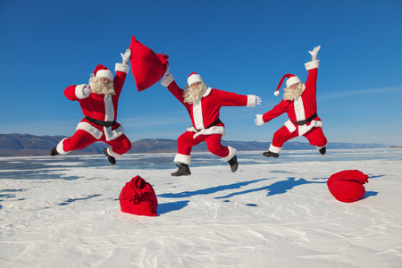 Three Jumping Santa Claus outdoors ,multiexposition, shooting was conducted in a sunny day on lake Baikal