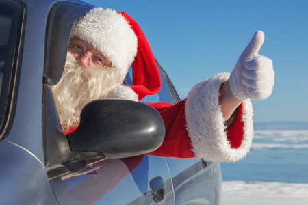 Portrait of Santa Claus in the car, raised thumb gesture