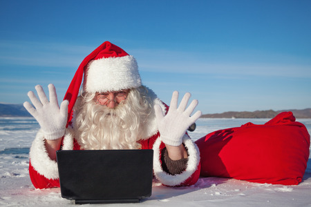 Santa Claus enjoys lying in the snow, looking at laptop news, shooting was conducted in a sunny day on lake Baikal