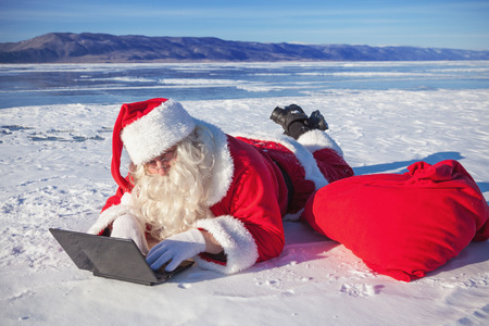 Santa Claus lying on the snow, looking at laptop news, shooting was conducted in a sunny day on lake Baikal photo