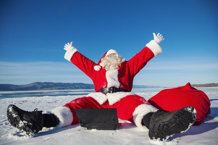Santa Claus sitting on snow glad news in the laptop, shooting was conducted in a sunny day on lake Baikal photo