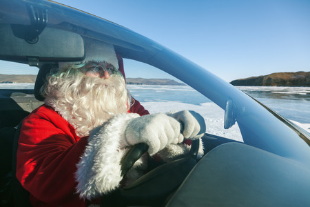 conducted:  Portrait of Santa Claus in the car, shooting was conducted in a sunny day on lake Baikal Stock Photo
