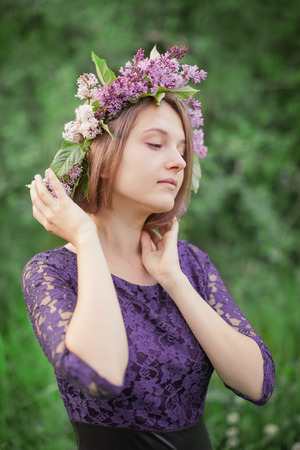 goodliness: Beautiful cute dreamy girl puts her hands wreath of lilac outdoors