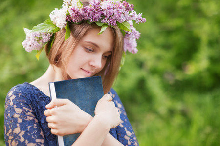 loveliness: A young girl in a wreath of lilac with a book in hand outdoors Stock Photo