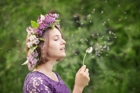 goodliness: Beautiful cute girl in a wreath of lilacs blowing on a dandelion outdoors