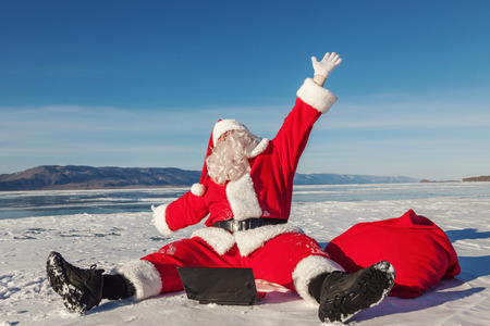 conducted: Santa Claus sitting on snow glad news in the laptop, shooting was conducted in a sunny day on lake Baikal Stock Photo