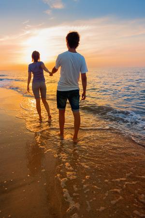 Chlapec a dívka jít na pláži při západu slunce