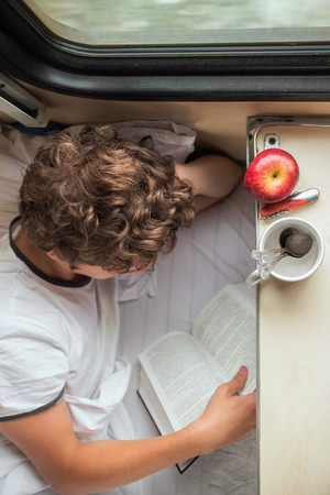 Teenager Boy reading a book on the train
