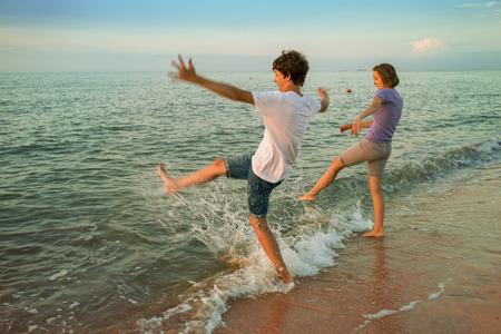 sprinkled: Boy and girl having fun sprinkled sea waves feet (blurred motion)