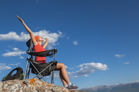 girl sitting in a camping chair on top of a mountain