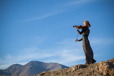 Girl in concert dress, playing the violin, standing on top of a mountain Banque d'images
