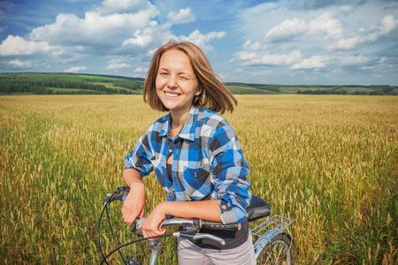Jednoduchý dospívající dívka na kole v letním poli