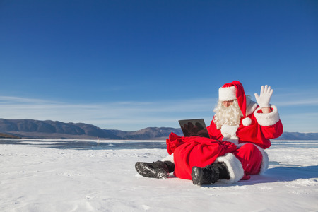 Père Noël assis sur la neige, en regardant ordinateur portable nouvelles, le tir a été effectué dans une journée ensoleillée sur le lac Baïkal Banque d'images - 32075793