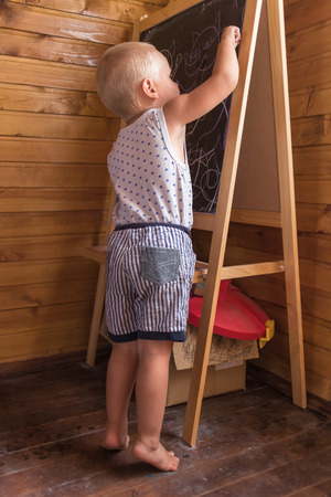 Young artist. Little boy drawing with chalk on a\ blackboard