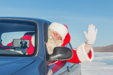 car on the road:  Portrait of Santa Claus in the car, shooting was conducted in a sunny day on lake Baikal Stock Photo