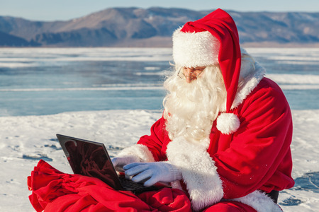 Santa Claus sitting on snow, looking at laptop news, shooting was conducted in a sunny day on lake Baikal
