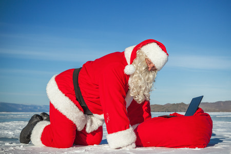 conducted: Santa Claus lying on the snow, looking at laptop news, shooting was conducted in a sunny day on lake Baikal Stock Photo