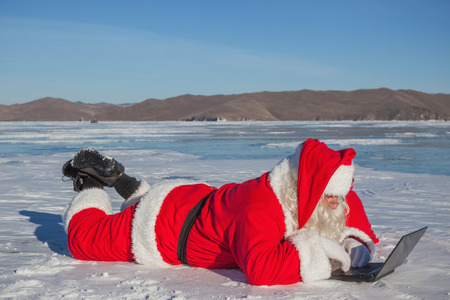 Santa Claus lying on the snow, looking at laptop news, shooting was conducted in a sunny day on lake Baikal Stock Photo
