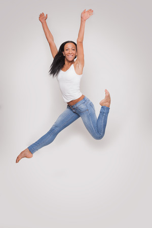 Young woman in white tank top and jeans jumping fun in the studio on a grey photo