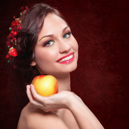 Beautiful young woman with evening make-up in the style of the summer with apple
