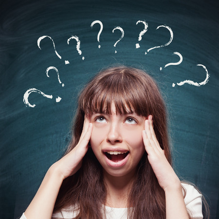 questions: Young girl with questioning expression and question marks above her head and blackboard in the background Stock Photo