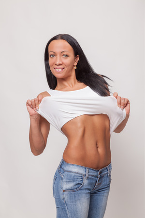trabalhar fora: Attractive young woman in jeans and a white T-shirt shows work out muscles in the abdomen