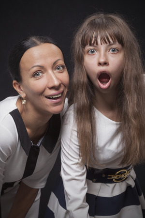 curiously: Young woman and her daughter curiously looking at the camera in a studio on a black background
