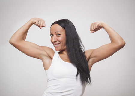 arm muscles: Young woman showing what her arm muscles on a grey