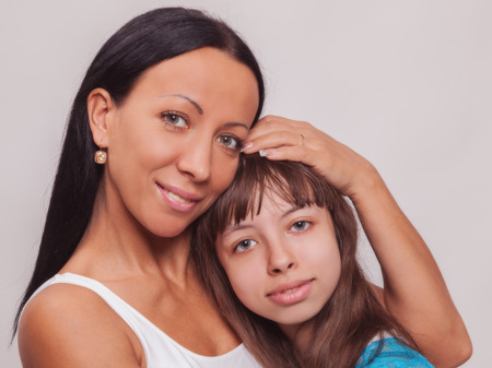 resemblance: Portrait of a mother and daughter, family hug on a white