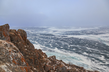 Rocks frozen into the ice of siberian Baikal Lake in winter photo