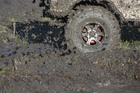insurmountable: The wheels of car go round on dirt road.