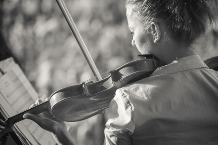 Portrait of a girl violinist, played in the orchestra in the summer in the open air