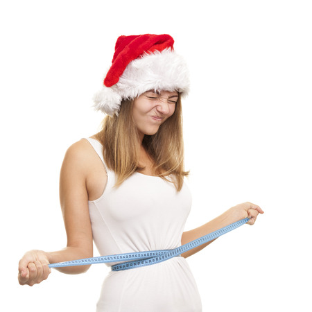 Girl in a red Santa's cap with a measuring tape around your waist