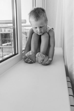 stared: little boy sitting on a windowsill and stared at his feet