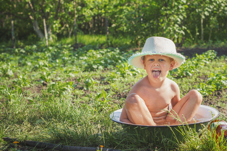 Little boy sits in a pelvis filled with water among the garden beds Stock Photo