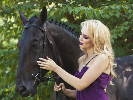 horse blonde: Outdoor portrait of a young blonde girl with long hair in a purple dress and a horse