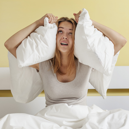 Teenage girl  sitting on bed and closing her ears with pillow