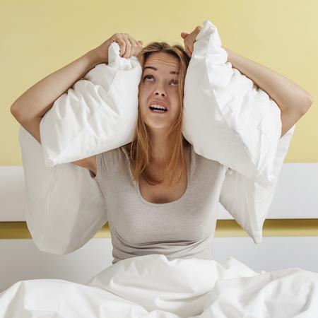 Une adolescente assis sur le lit et la fermeture de ses oreilles avec l'oreiller Banque d'images - 63741284